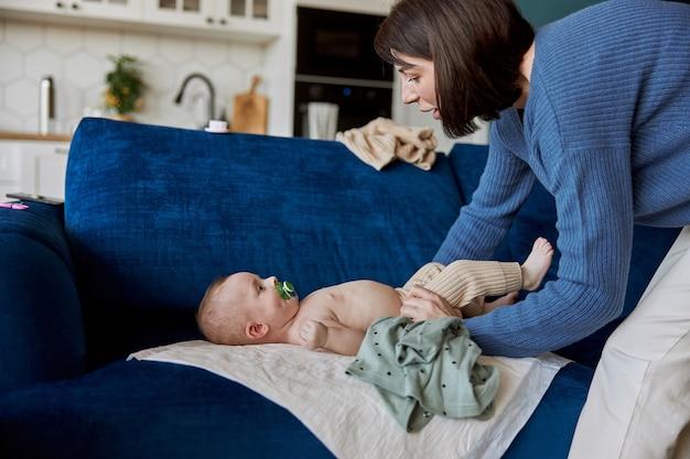 Мать одежда новорожденного девочку на подкладке на софе. вид сбоку младенца с соской во рту и молодой женщины. интерьер однокомнатной квартиры. понятие материнства и ухода за ребенком