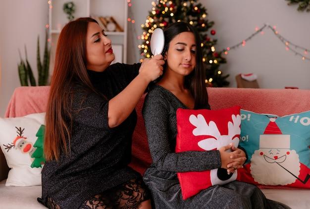 집에서 크리스마스 시간을 즐기고 소파에 앉아 어머니 빗질 딸 머리