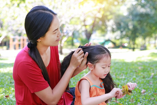 Mother combing daughter's hair lying in the green garden.