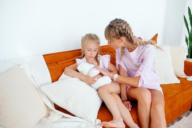 Мать утешает девочку, сидя на диване в светлой комнате, когда возникают проблемы. девочка держит белого плюшевого мишку