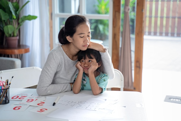 Mother comforts her upset daugther at home