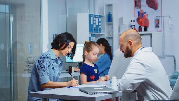 의료 사무실에서 딸 데이터로 의료 설문지를 작성하는 어머니. 병원 캐비닛에서 의료 서비스 상담 진단 검사 치료를 제공하는 의학 전문가