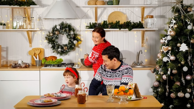 Mother cooks festive supper and smiling father sits with cute girl kid at table in kitchen near decorated new year tree