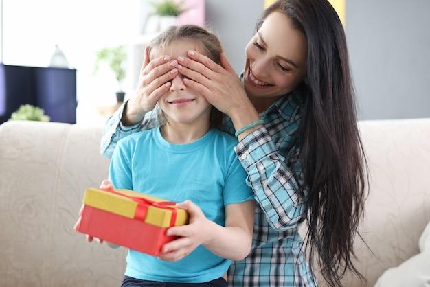 그녀의 손으로 그녀의 딸 눈을 덮고 어머니 선물 상자를 들고 어린 소녀