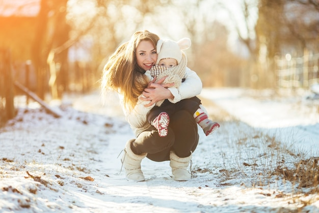 Mother crouching with her little boy in her arms on a snowy street