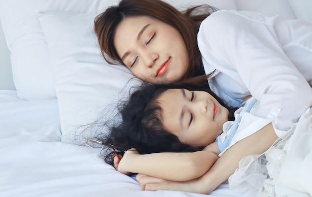母は愛情を込めてベッドで娘を抱きしめた