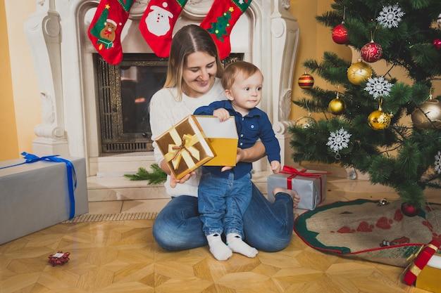 クリスマスツリーで彼女の男の子を抱きしめる母