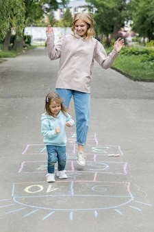 Mother and cute child playing hopscotch