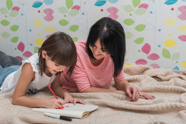 Mother and cute daughter drawing lying on bed