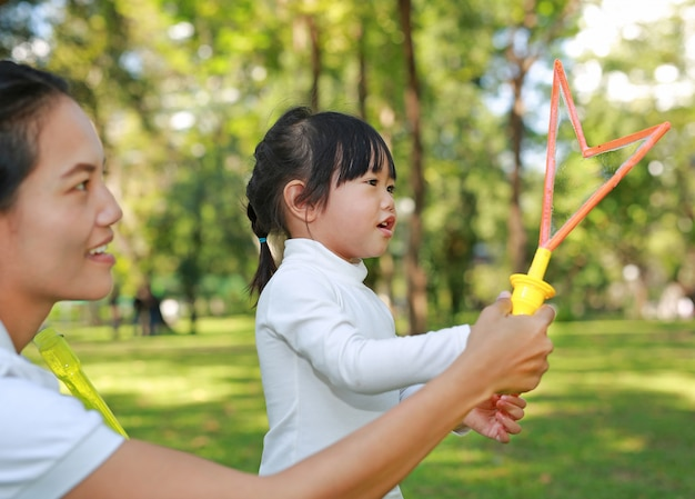 Mother and cute little girl playing bubble in the park.