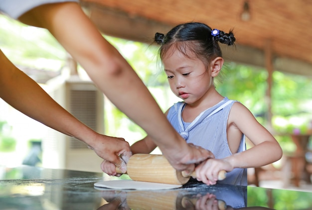 Mother and cute little girl using wooden rolling pin