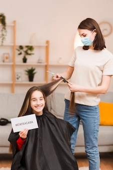 Mother cutting daughter hair