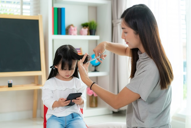 Mother cutting hair to her daughter in living room at home while stay at home.