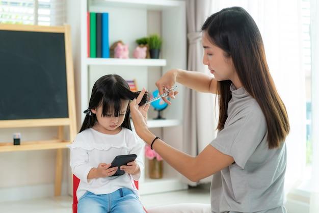 Мать стрижет волосы дочери в гостиной дома, оставаясь дома.