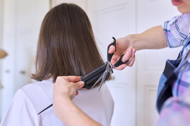 Мать стрижет волосы дочери-подростку, красота и уход в домашних условиях.