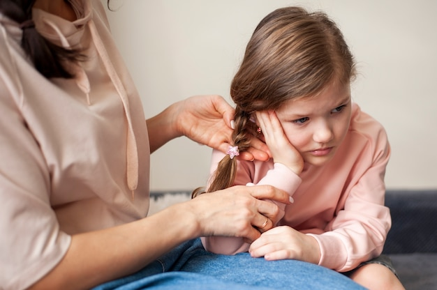 Мать подстригает волосы молодых девушек