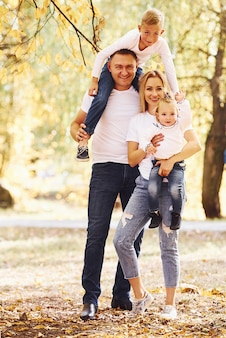 Mother and dad holds kids at shoulders and in hands. cheerful young family have a walk in an autumn park together.
