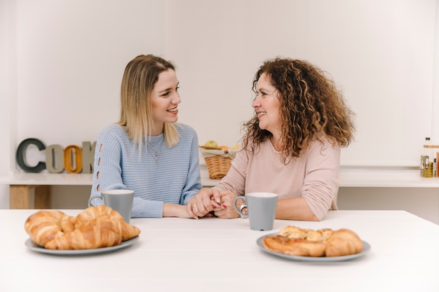Mother and daugher holding hands during breakfast