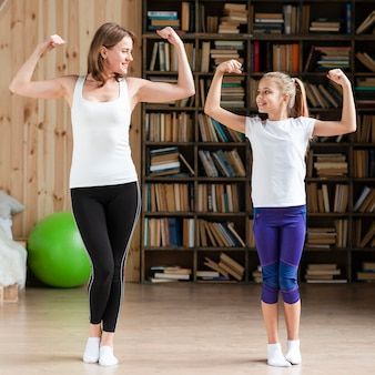 Mother and daughhter flexing muscles