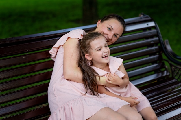 Mother and daughter 5-6 years old walking in the park in the summer, daughter and mother laughing on a bench, the concept of a happy family, the relationship of mother and child, mother's day