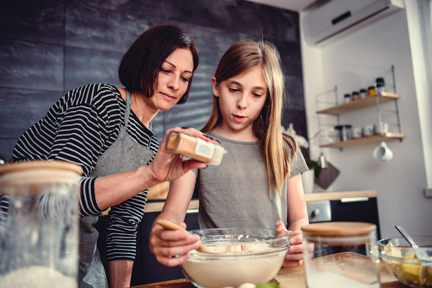 Mother and daughter adding cinnamon into mixing bowl