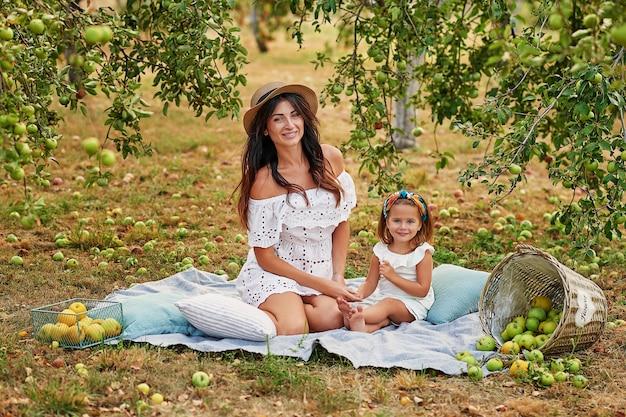 Mother and daughter in apple garden