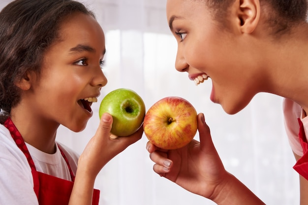 Mother and daughter in aprons eat apples in kitchen.