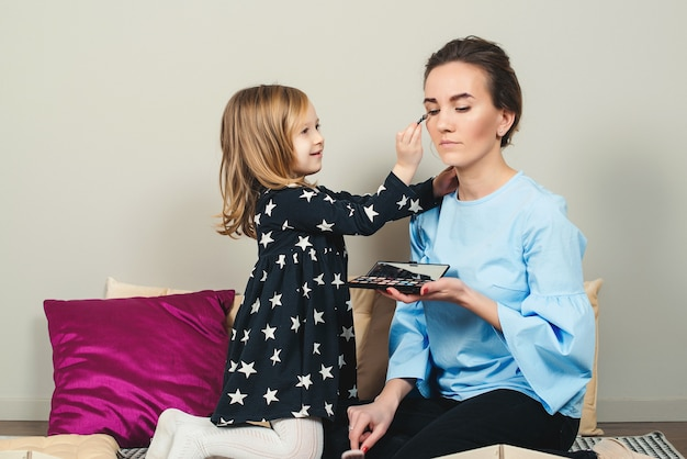 Mother and daughter are doing makeup. lovely mom and child having fun together. happy mother's day.