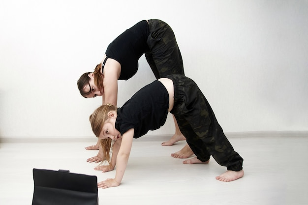 Mother and daughter are doing yoga online