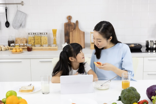 Mother and daughter are eating breakfast and watching media in a tablet