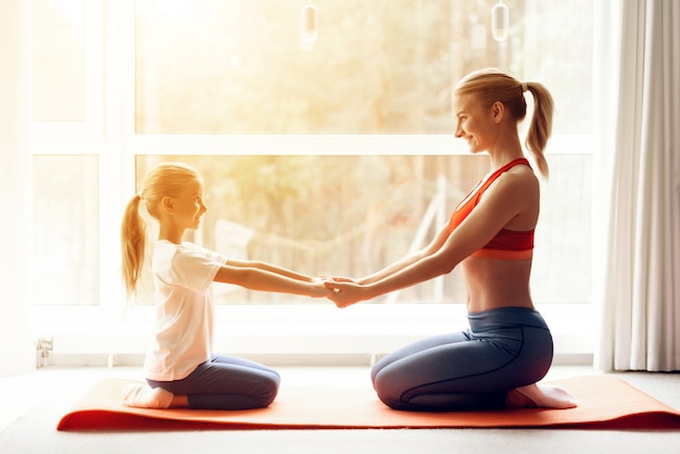 Mother and daughter are engaged in yoga in sportswear.