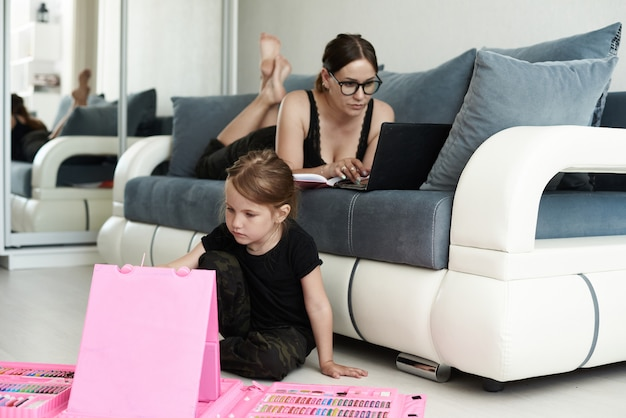 Mother and daughter are at home. mother and daughter are working at home.