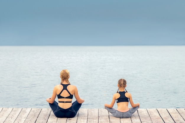 Mother and daughter are meditating by the sea at pier