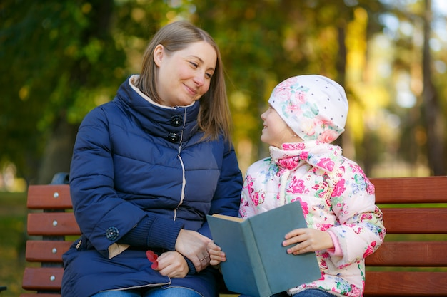 Mother and daughter are reading book and having fun in nature