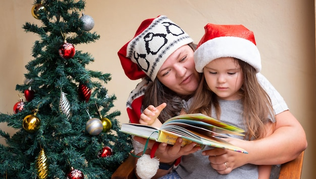 Mother and daughter are reading a book sitting in a chair near the christmas tree in santa hat