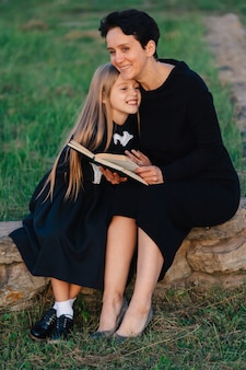 Mother and daughter are sitting on a stone bench and reading a book. woman with a child in black dresses.