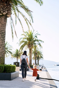 Mother and daughter are taking a walk by the palm trees in a marina in montenegro.
