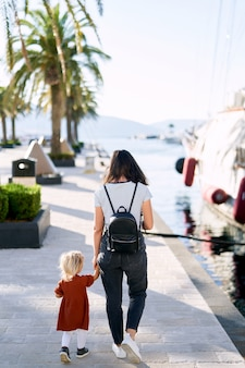 Mother and daughter are walking hand in hand on a boat pier in porto montenegro.