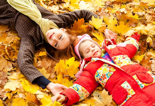 Mother and daughter in autumn yellow park