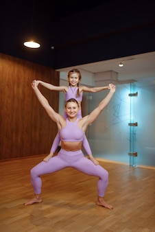 Mother and daughter, balance exercise in gym, yoga workout. mom and little girl in sportswear, woman with kid on joint training in sport club
