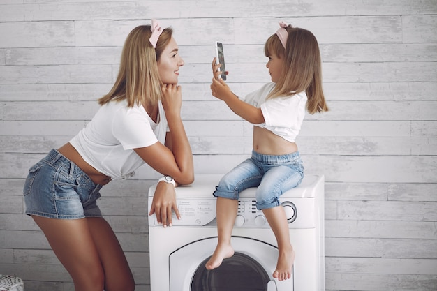 La madre e la figlia in un bagno vicino lavano il mashine