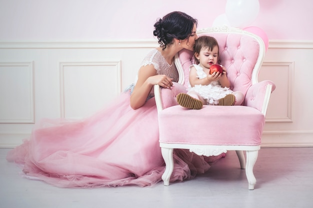 Mother and daughter a beautiful and happy pink interior with vintage chair and balls in beautiful dresses holiday