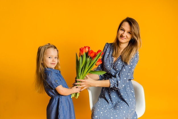Mother and daughter in blue dresses with a bouquet of red tulips on a yellow wall