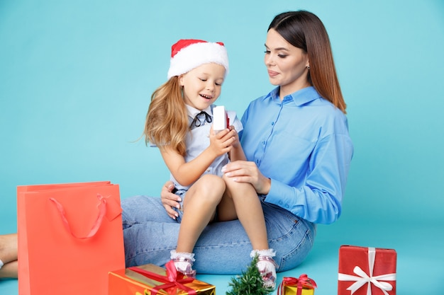 Mother and daughter in blue shurt with gifts together.