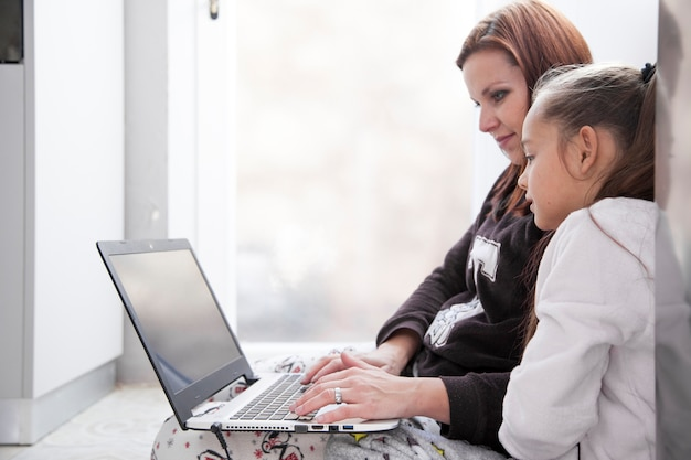 Mother and daughter browsing laptop on floor