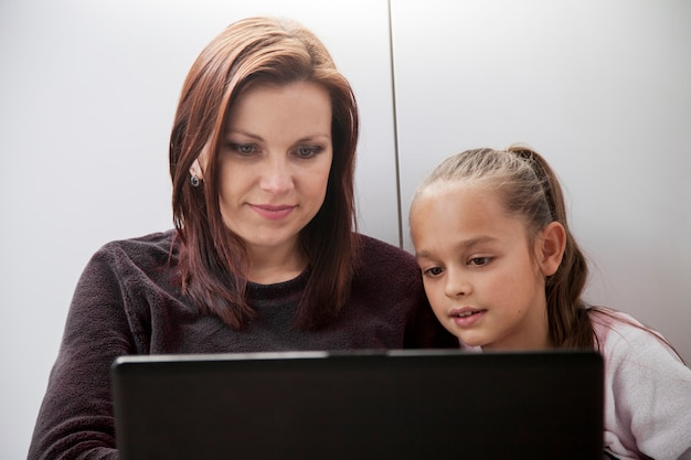 Mother and daughter browsing laptop