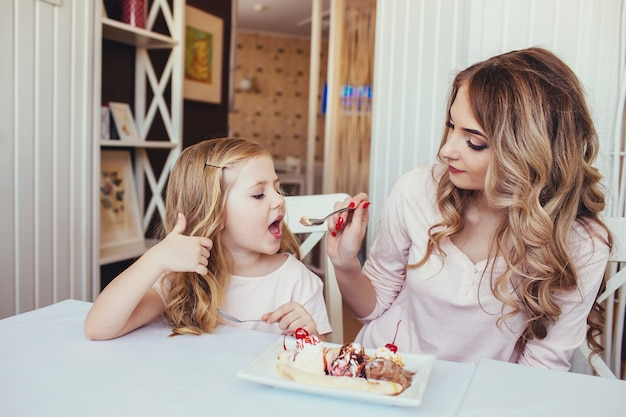 Mother and daughter in a cafe sitting at a table and feed each other ice cream.
