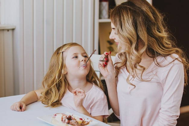 Mother and daughter in a cafe sitting at a table and feed each other ice cream