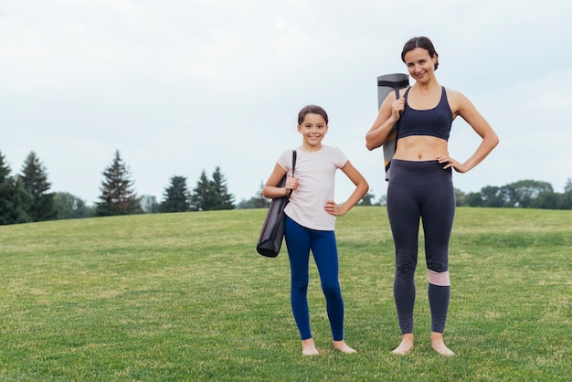 Mother and daughter carrying yoga mats