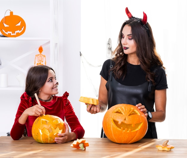 Mother and daughter carving pumpkins for halloween
